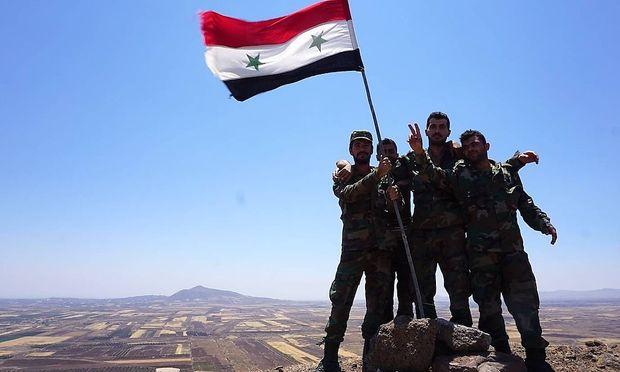 Soldaten der syrischen Regierung hissen die syrische Flagge in Al-Mal in der südlichen Provinz Quneitra.
