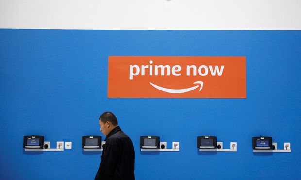 A man passes an Amazon Prime Now signage at their fulfillment centre in Singapore