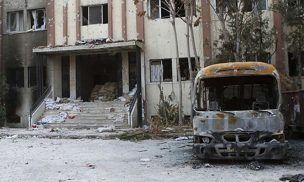 A burnt bus is seen in front of a damaged building in the Damascus suburb of Douma