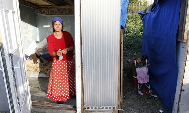 A Roma woman stands in the doorway of her shelter in an illegal camp in Croix