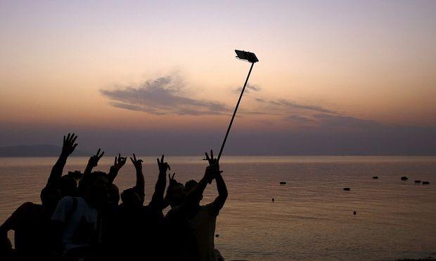 Neue Technologien verändern uns. Das Foto zeigt syrische Flüchtlinge im August 2015, die nach der Ankunft auf der griechischen Insel Kos ein Selfie machen.