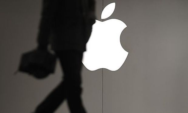 A man walks pass the Apple logo outside an Apple store in Shanghai