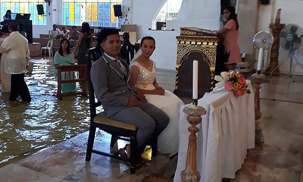 Das glückliche Brautpaar in der überschwemmten Kirche
