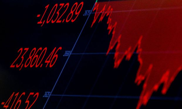 A screen displays the Dow Jones Industrial Average after the closing bell on the floor of the NYSE in New York