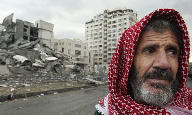 A Palestinian man walks past a Hamas government building destroyed after an Israeli air strike in Gaza