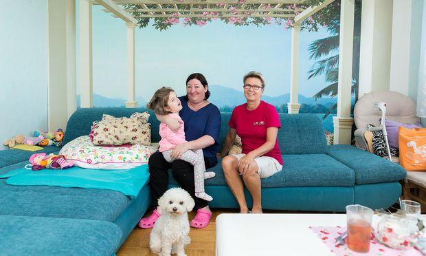 Elisa auf dem Schoß ihrer Mutter, Jasmin Haberda-Korntheil. Eine Kinderkrankenpflegerin von Moki Wien unterstützt beide mehrmals die Woche.