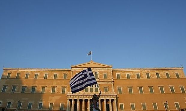 A woman raises a Greek flag during a rally against austerity in front of the parliament at Constituti