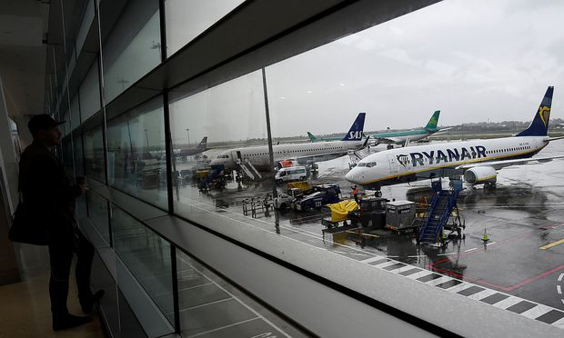 FILE PHOTO: A man looks out at a Ryanair plane in the Departures lounge at Dublin airport in Dublin