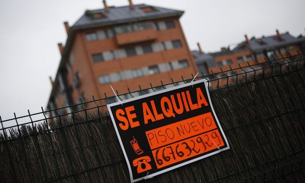 A sign that reads: 'New flat for rent' is hung outside a block of houses on the outskirts of Madrid