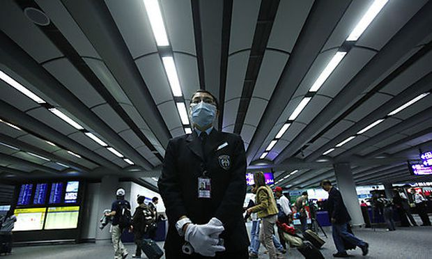 A health worker stands by ready to ask incoming passengers to remove any head gear prior to temperatu