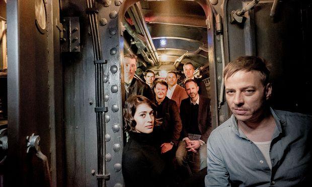 """Noch fehlen Szenebilder, auch deshalb muss die Crew der """"Das Boot""""-Neuauflage zum gestellten Gruppenfoto im Inneren des U-Bootes antreten. Vorn links: Lizzy Caplan, vorn rechts: Tom Wlaschiha."""