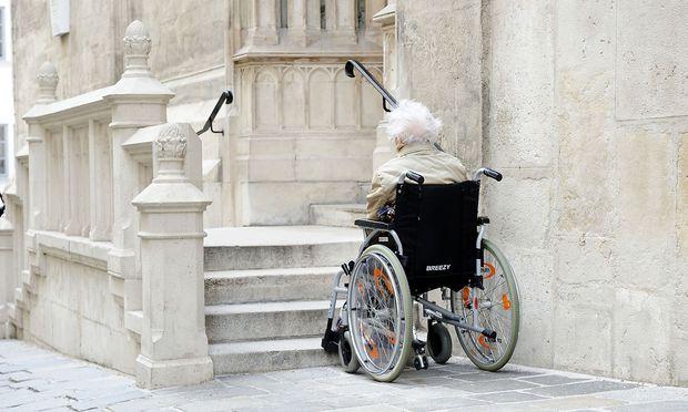 Rollstuhlfahrerin vor einer Treppe (Symbolbild)