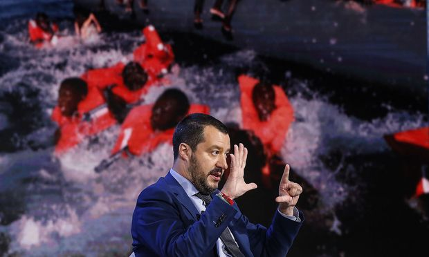 Italiens Innenminister, Matteo Salvini, hier in einer TV-Show, die im Hintergrund Bilder von Bootsflüchtlingen zeigt. Der Lega-Politiker fordert bei der Migration mehr Solidarität von der EU.