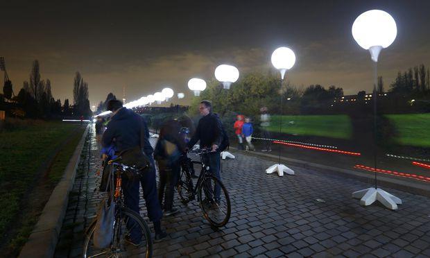 Zehntausende Berliner und Touristen aus aller Welt promenierten am Wochenende – wie hier im Regierungsviertel an der Spree – entlang der ehemaligen Grenze, die leuchtend weiße Ballons markierten. / Bild: (c) REUTERS (PAWEL KOPCZYNSKI)