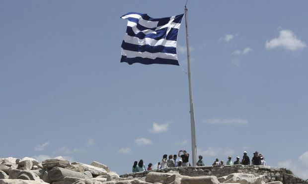 A Greek flug flutters at the top of the Acroplis hill in Athens
