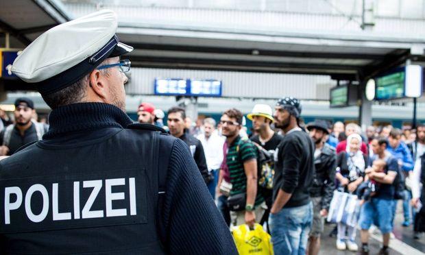Muenchen Ein Bundespolizist vor einer Gruppe von akommenden Fluechtlingen Copyright Gehrling E