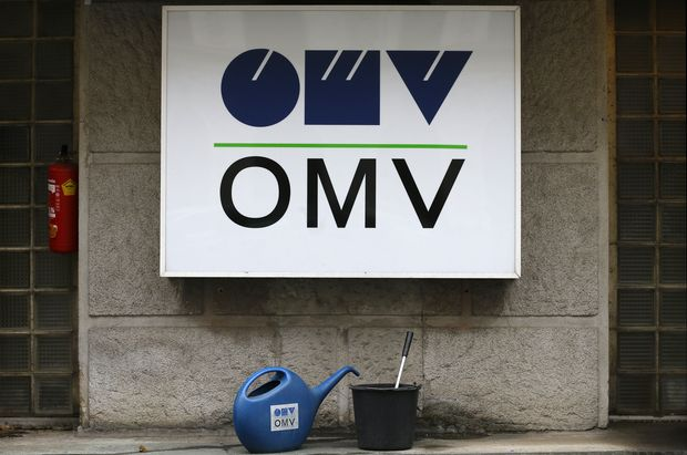 Watering cans are palced in front of the logo of Austrian energy group OMV at a gas station in Vienna