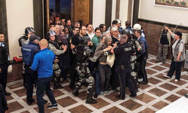 Gewalt im Parlament. Mazedonische Polizisten versuchen die Schlägertrupps zu stoppen, die in das Gebäude der Volksvertretung in Skopje eingedrungen sind.