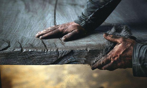 Nach dem Köhlen wird das Holz händisch gebürstet und pigmentiert.