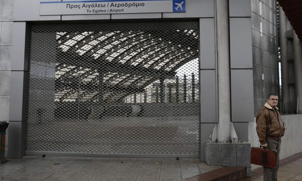 A commuter stands outside a closed metro station during a 24-hour strike of workers at the Athens Metro, tram, suburban railway and city train in Athens