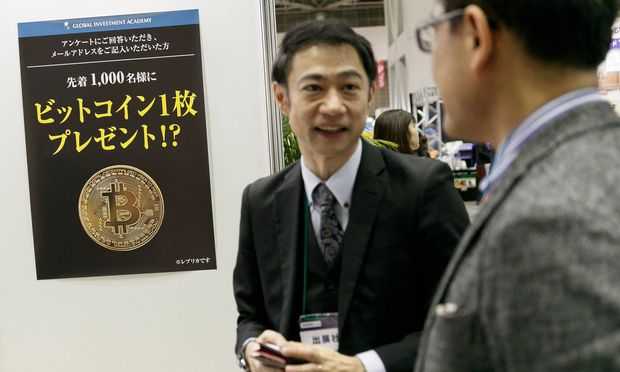 An exhibitor speaks about cryptocurrency Bitcoin to a visitor during the 1st Asset Management Expo o