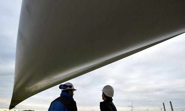 Technicians stand under a rotor wing of a giant wind generator during its assembly on a construction..