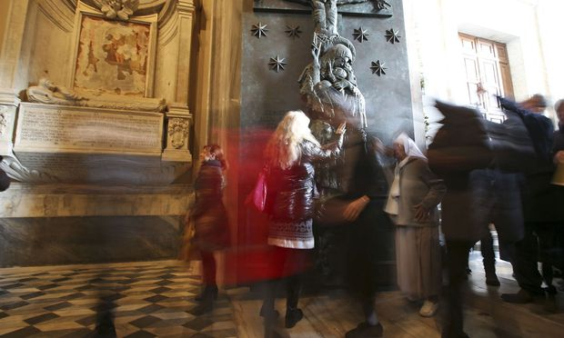 Faithful cross the the Holy Door opened by Pope Francis in Saint John Lateran basilica in Rome