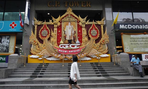 A woman walks outside the CP Tower in Bangkok