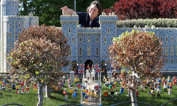 Head model maker, Paula Laughton poses for a photograph with a LEGO Windsor Castle replete with royal wedding between Britain´s Prince Harry and Meghan Markle, in Windsor