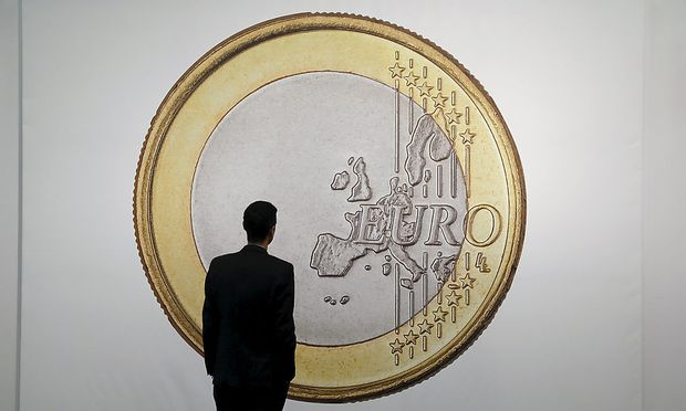 A man is silhouetted against 'SUPERFLEX, Euro 2012', a 416.6 cm by 289.6 cm (164 by 114 inch) large photographic print of an Euro coin on sale by the Los Angeles based gallery 1301 PE at the Art Cologne 2015 fair in Cologne