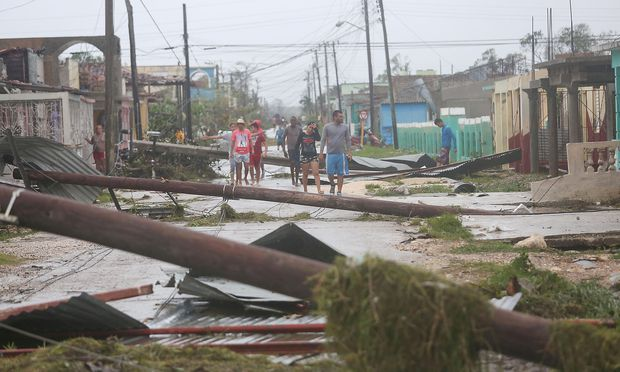 People walk on a damaged street after the passage of Hurricane Irma in Caibarien, Cuba