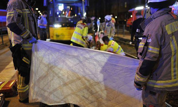 Feuerwehrmänner halten nach einem Unfall eine Sichtblende gegen Schaulustige hoch