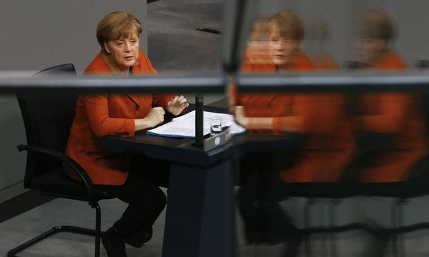 German Chancellor Merkel is reflected in glass fence at German  Bundestag in Berlin