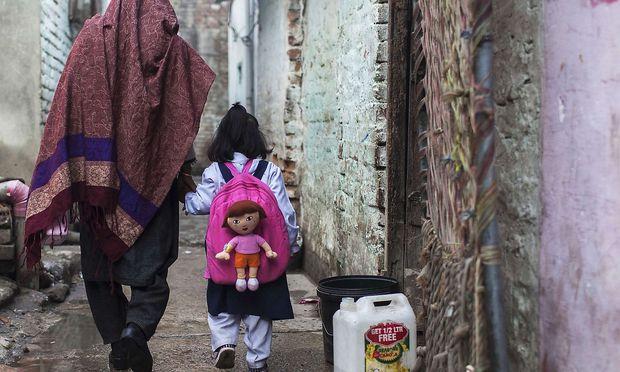 Eine Mutter, die ihr Kind in die Schule bringt.