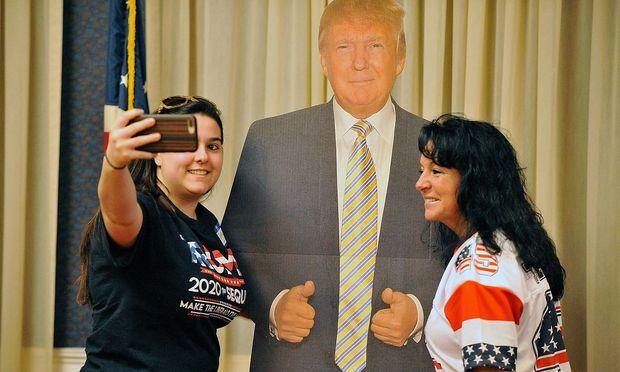 Zwei Trump-Anhängerinnen machen ein Foto mit einem Papp-Präsidenten bei einem Wahlkampf-Event in Massachusetts.