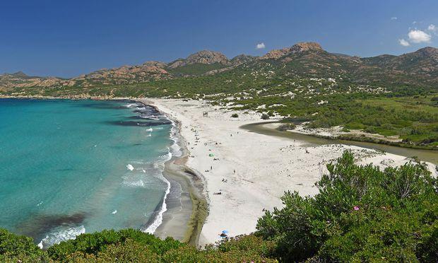 Türkis-blaues Wasser an einem Sandstrand von Korsika.
