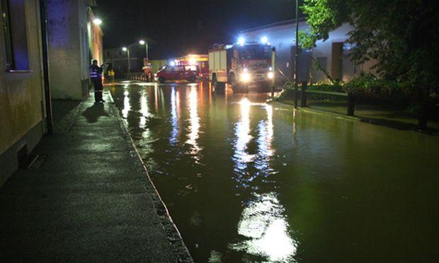 Einsatzkräfte der Feuerwehr bei einer überschwemmten Straße in St. Pölten.