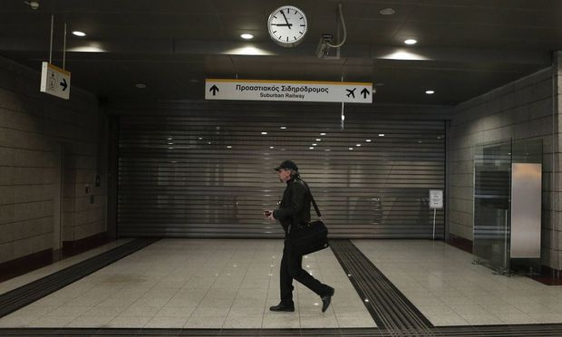 A man walks in front of a closed entrance of a suburban station during a 24-hour strike in Chalandri suburb north of Athens