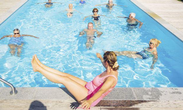 Group of seniBewegung ist eines der zentralen Ziele der neuen Kur.rs with trainer doing water gymnastics in pool
