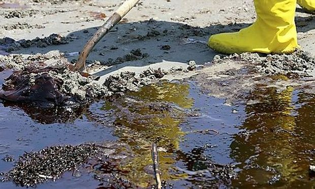 Oil clings to a shovel as workers clean up the oil contaminated beach in Port Fourchon, Louisiana