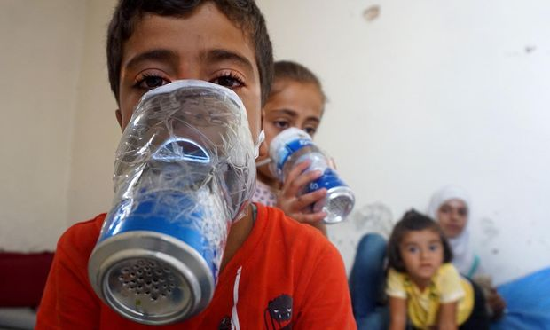 Kinder in der nordsyrischen Rebellenbastion Idlib mit improvisierten Gasmasken, die aus Getränkedosen gebastelt sind.