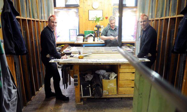 Der gedoppelte Reinhard Bauer an seiner Werkbank. Dort wird gerade an einer in ihre Einzelteile zerlegten Jugendstil-Stiegenhausverglasung gearbeitet.
