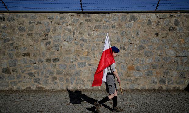 Ein Scout aus Polen trägt eine polnische Nationalflagge an der Gedenkstätte des ehemaligen Konzentrationslagers Mauthausen
