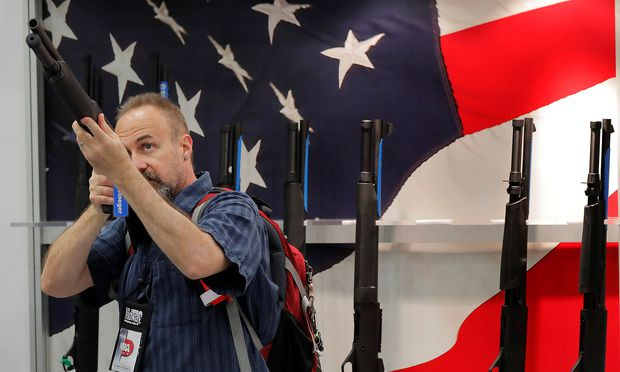 A gun enthusiast looks at a shotgun during the annual National Rifle Association (NRA) convention in Dallas, Texas