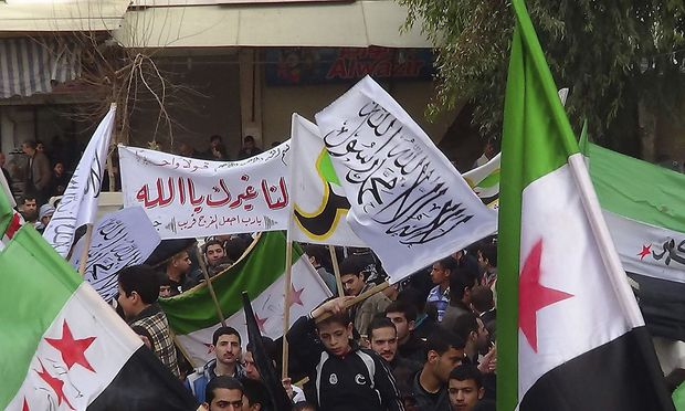 Demonstrators hold opposition flags during a protest against Syria's President Bashar al-Assad, in Jubar