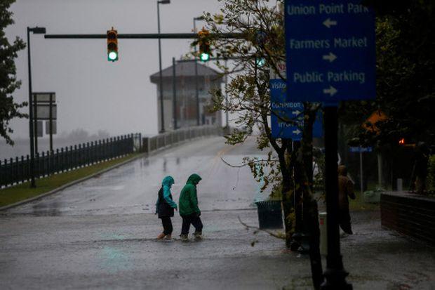 Menschen stapfen auf einer überschwemmten Straße in der Stadt New Bern im US-Bundesstaat North Carolina.