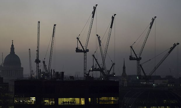 Offices are seen at dusk as St. Paul's cathedral and construction cranes are seen on the skyline in the City of London