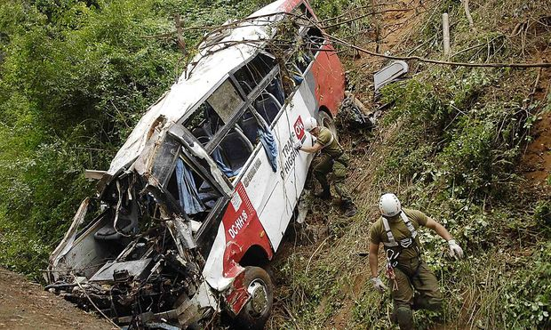 Policemen inspect a passenger bus after an accident along Route CH-150, known as Cuesta Caracol, in Tome city near Concepcion