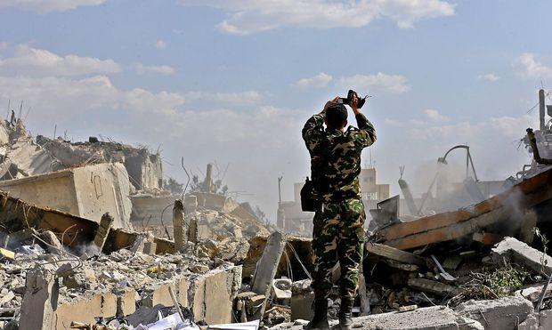 Syrischer Soldat vor den Ruinen des Barzeh-Forschungskomplexes in Damaskus