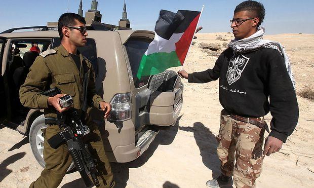 Konfronation in der Westbank. Ein palästinensischer Aktivist versucht auf einem israelischen Militärfahrzeug eine Palästinenserfahne anzubringen.
